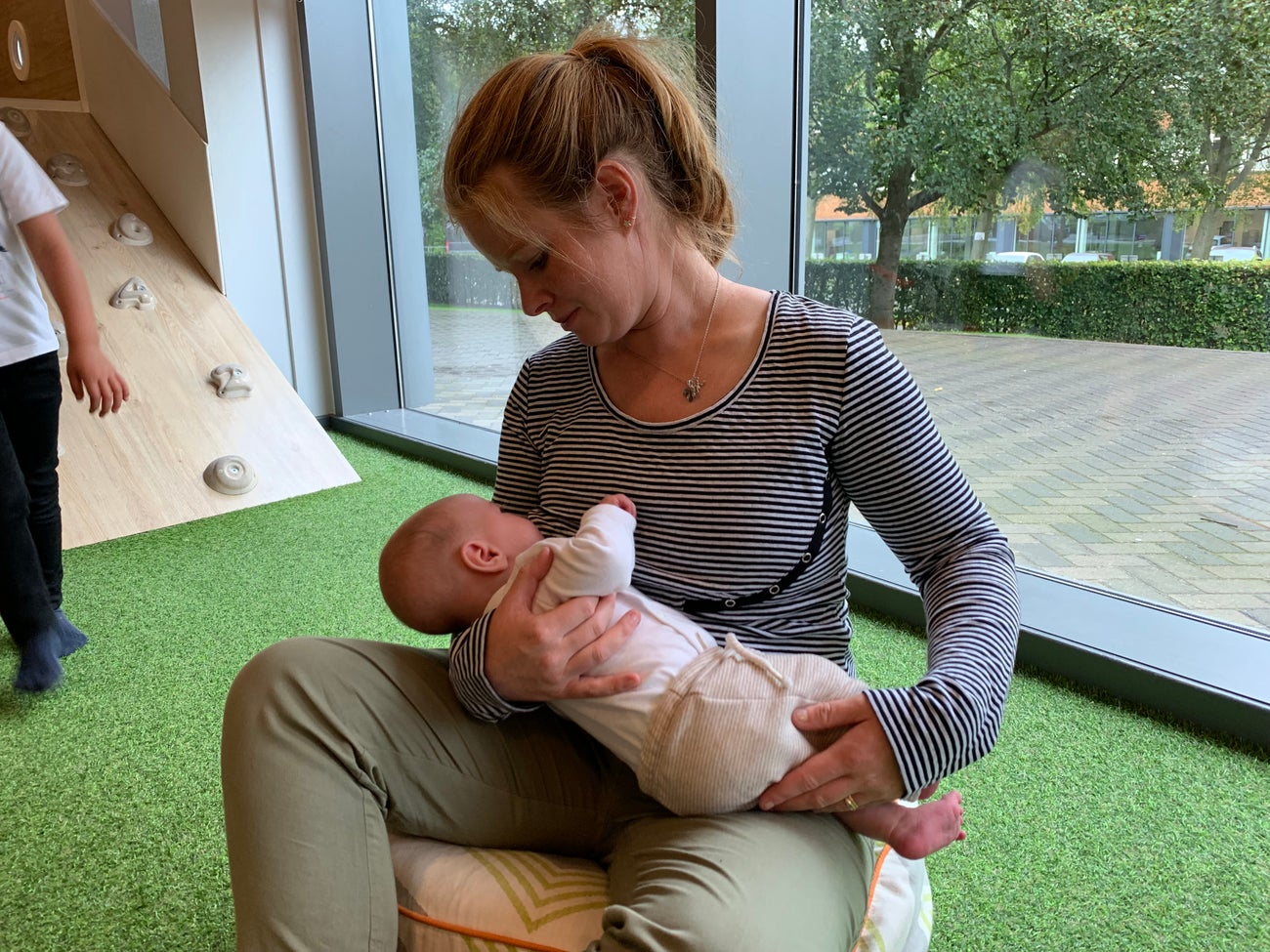 Woman feeding baby wearing Peekaboobie cotton nursing or breastfeeding top